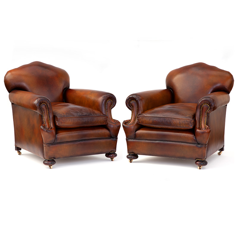 Fabulous pair of double scroll arm leather camel back club chairs on ball feet with brass castors. c.1920.