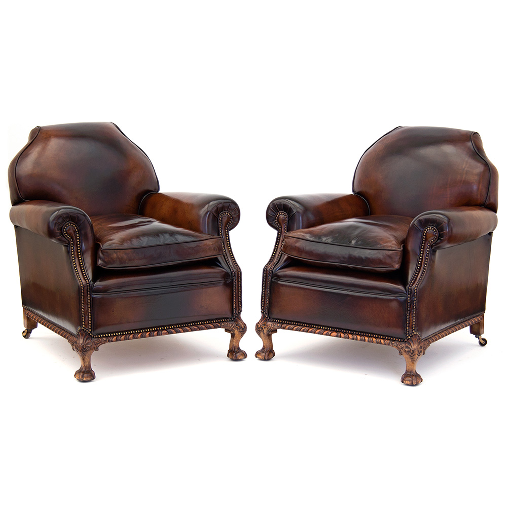 Superb pair of large leather club chairs raised on walnut claw and ball feet on carved frieze. Circa 1900.